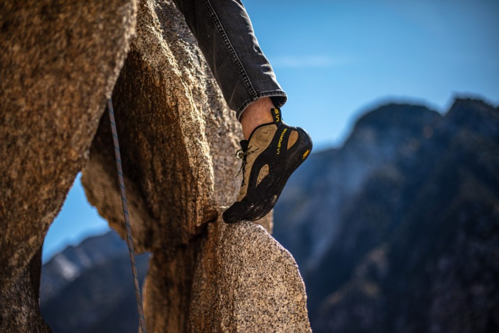 man climbing the rock formation during daytime